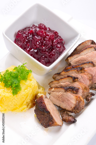 Roasted duck breast with potatoes and cranberry sauce