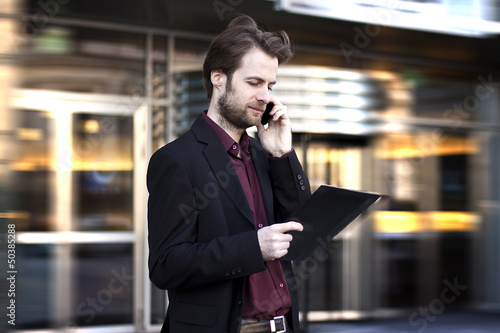 Businessman outside office building talking on a mobile phone