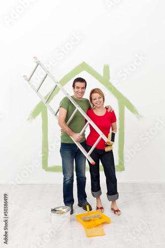 Happy couple painting their home