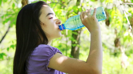 Young girl drinking water out of a plastic bottle outside