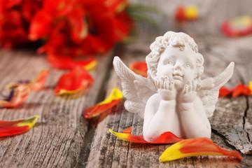 Weißer Engel mit aufgestützten Händen vor roten Blüten