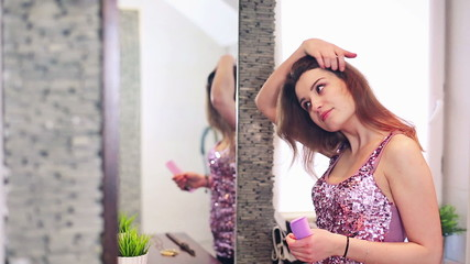 Young woman combing her beautiful long hair before party