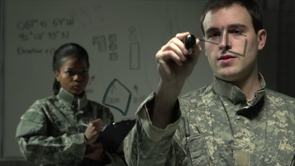 Soldier strategizing with fellow soldier using a board
