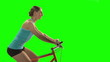 Young woman biking profile shot on green screen.
