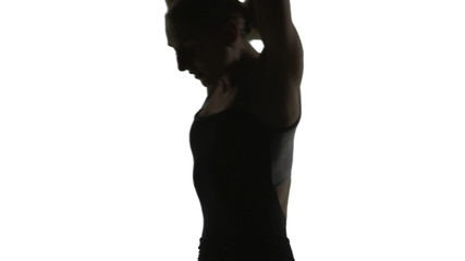 Silhouette of a Young woman dancing front of a white screen.