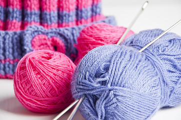 Two knitting needles, woolen yarn clew and knitting cap
