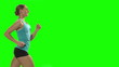 Woman running on the treadmill. Green screen, profile