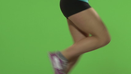 Woman running on the treadmill. Green screen. Close up of legs.