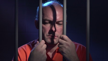 Man behind bars reflecting on his crime