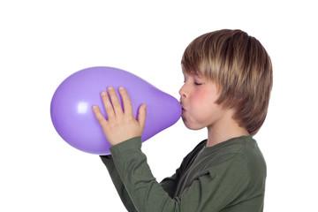 Adorable preteen boy blowing up a purple balloon