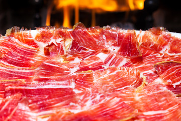 plate of Spanish jamon iberico sliced with a fireplace as back