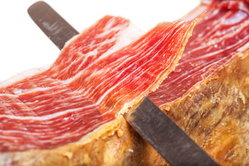 Slicing Spanish jamon iberico (ham) on white background