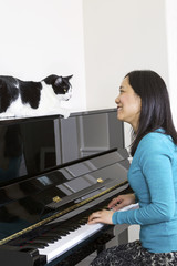 Mature woman and her cat looking at each other during piano sess