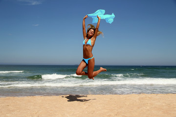 beautiful tanned woman jumping on the beach.
