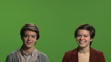 Twin sisters in front of clean green screen with room for text
