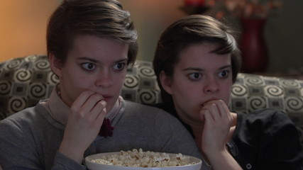 Twin sisters watching a horror movie together, eating popcorn