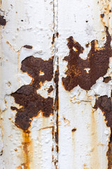 Close up of white paint pealing off of metal with rust stains