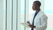 African American doctor going over charts, looking out window