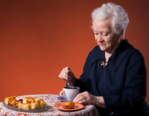 Old woman enjoying  tea cup with apple pie