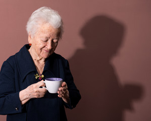 Old woman enjoying coffee or tea cup over brown background