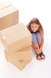 Cute little girl is hiding behind boxes