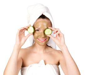Frau hält sich Gurkenscheiben vor die Augen
