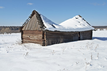 Old wooden barn under snow