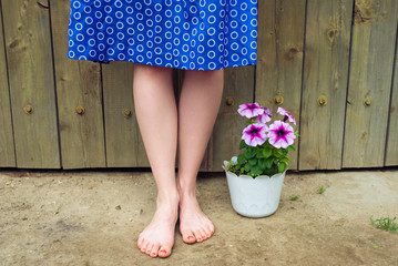 Female legs and a pot of flowers.