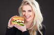 Hübsche junge Frau mit Hamburger lächelt