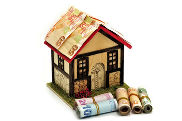 Small house isolated on a white background and rolls of money