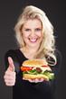 Hübsche junge Frau mit Hamburger lächelt Daumen hoch
