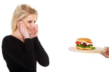 Hübsche junge Frau freut sich über Hamburger und lacht