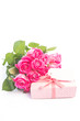 Bouquet of roses next to a gift with a blank card
