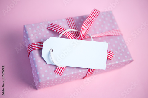 Pink gift wrapped box with blank tag