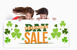 Girls holding placard with st patricks day sale text