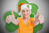 Girl in orange t-shirt giving thumbs up on shamrock background