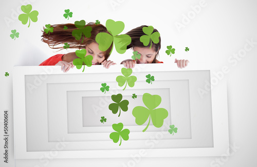 Girls looking down at placard with shamrocks