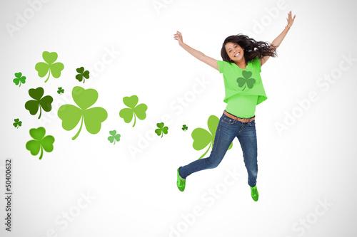 Girl wearing green shamrock t-shirt jumping for joy