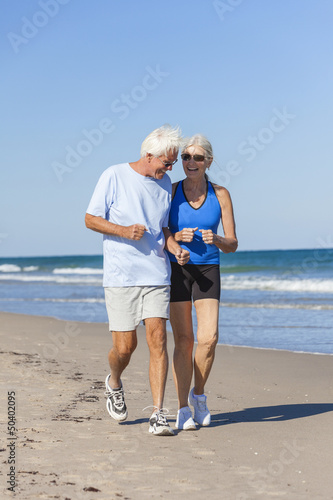 Healthy Senior Couple Running Jogging on Beach