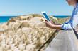 frau am strand schaut auf tablet-pc