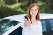 glückliche junge frau zeigt ihren autoschlüssel
