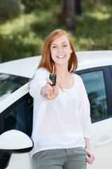 lachende junge frau zeigt autoschlüssel
