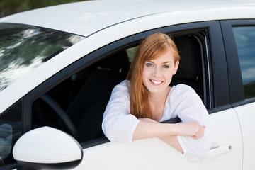 lächelnde junge frau sitzt in ihrem auto