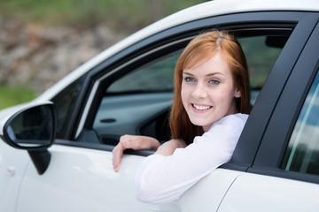 lächelnde frau schaut aus dem autofenster