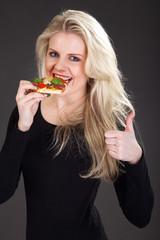 Junge blonde Frau isst Pizza und lacht Daumen hoch