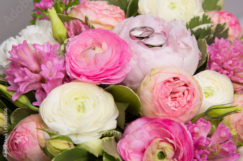 wedding rings on bouquet of white and pink peonies