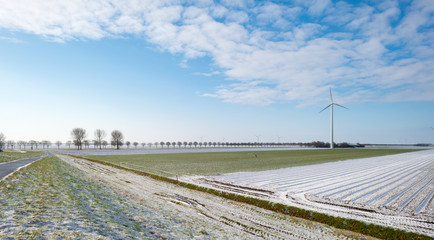 Wind turbine in a snowy field in sunlight