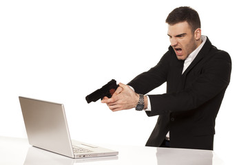 young businessman destroying his laptop using guns