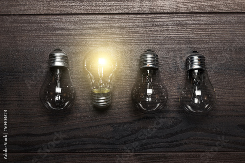 glowing bulb uniqueness concept on wooden background - 50403623