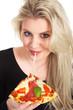 Junge blonde Frau isst Pizza und zieht Käsefäden